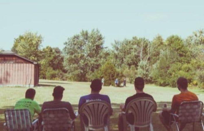 men sitting in backyard