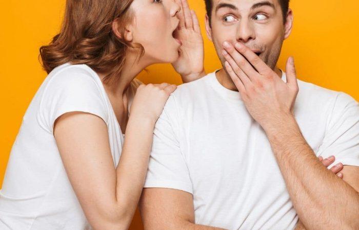 woman telling man secret